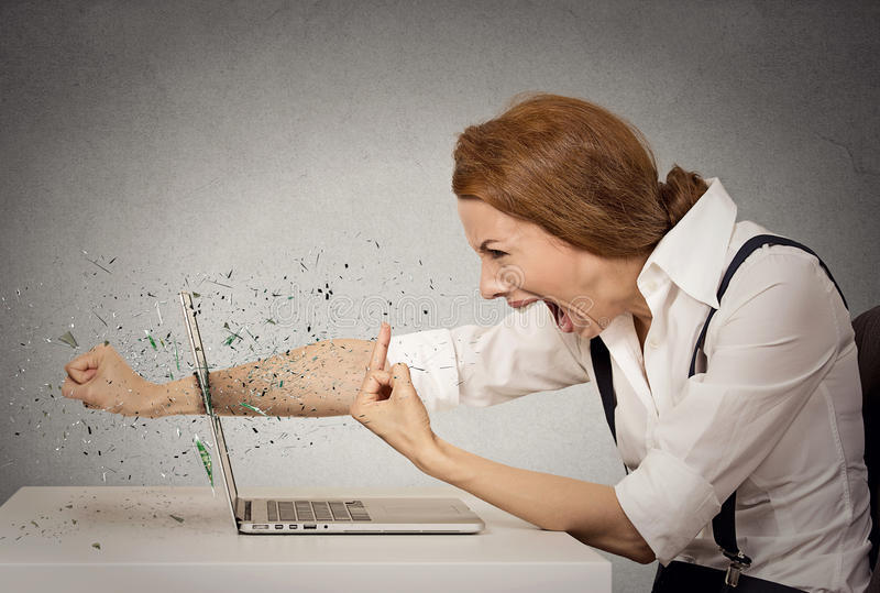 Angry business woman throws punch into computer, screaming. Side profile angry furious businesswoman throws a punch into computer, screaming. Negative human royalty free stock photography