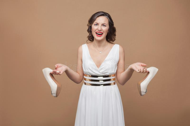 Angry business woman in white dress standing looking at camera s. Creaming and holding uncomfortable high heels. Emotion and feeling concept. Studio shot, indoor royalty free stock images