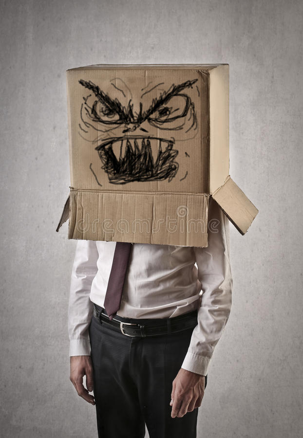 Angry businessman with a box on his head royalty free stock photo