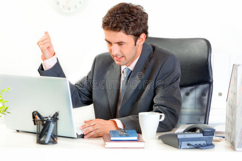 Angry businessman brandishing fist on laptop. Angry modern businessman sitting at office desk and menacingly brandishing his fist on laptop royalty free stock image