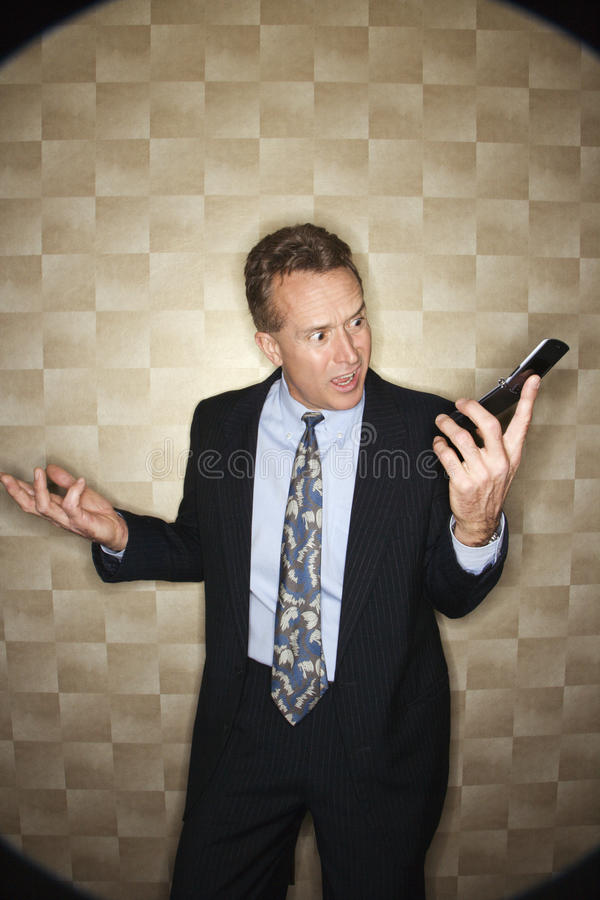 Angry Businessman on Cell Phone royalty free stock photography