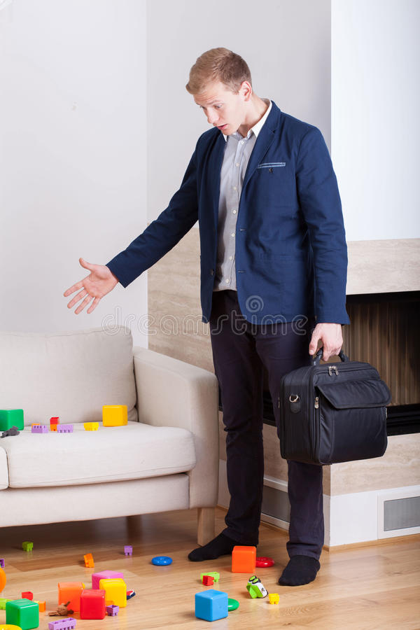 Angry businessman coming back home. And see mess stock image