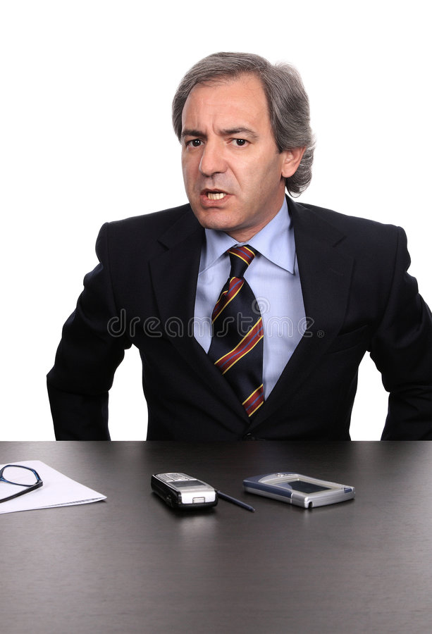 Angry businessman debating. Firmly at his desk isolated on white stock photos