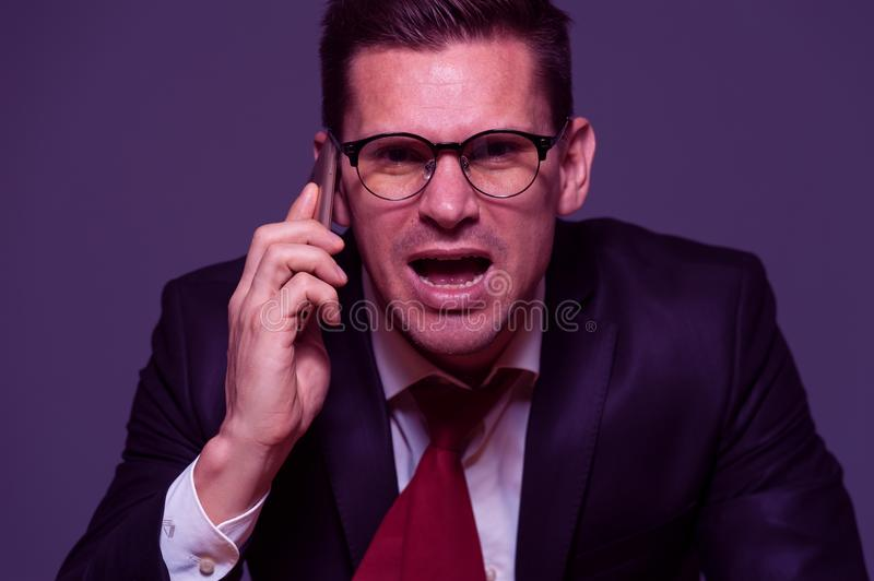 Angry businessman furiously talking on the phone. Portrait in purple tone - angry young businessman in glasses and formal clothes furiously talking to someone on stock images