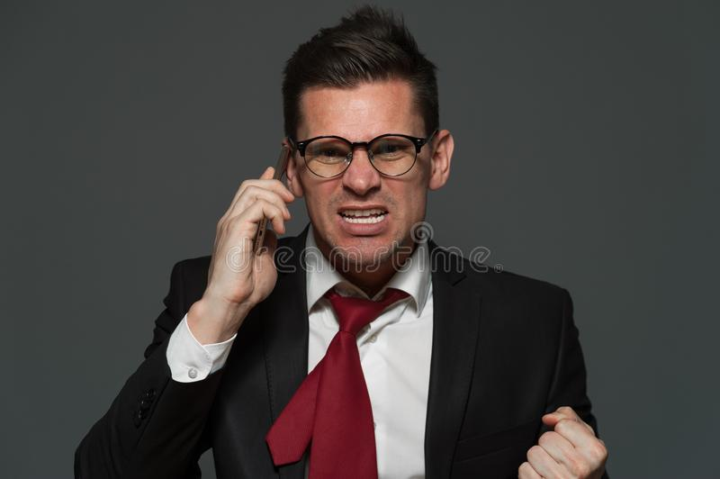 Angry businessman furiously talking on the phone. Stress at work. An upset businessman talks on the phone about ruptured deal on gray background royalty free stock photos