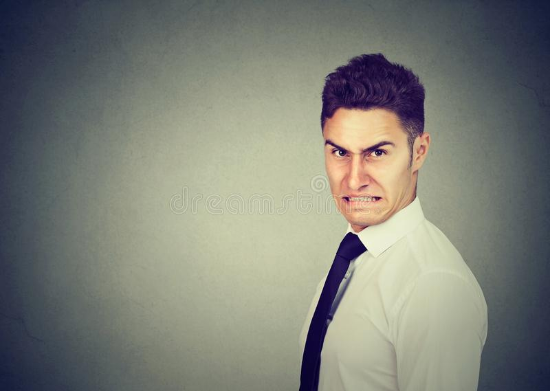 Angry businessman grinning at camera royalty free stock photo