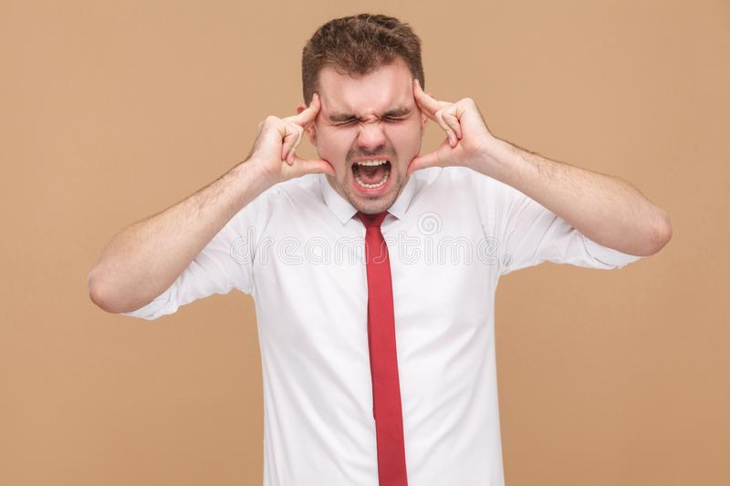 Angry businessman have migraine and headache. Business people concept, good and bad emotion and feelings. Studio shot, on light brown background stock photo