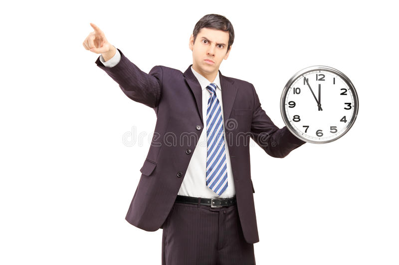 Angry Businessman Holding A Clock And Pointing With A Finger Stock Photos
