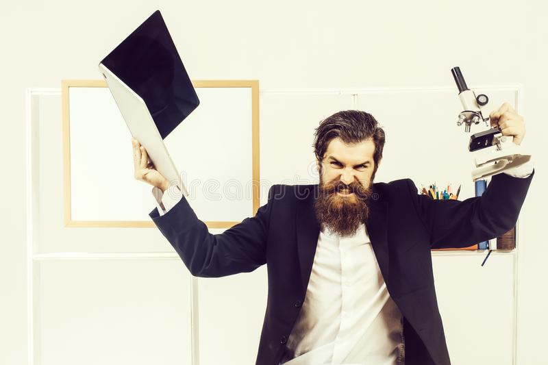 Angry businessman with laptop. Angry man businessman male scientist hipster with laptop and microscope shouts furiously in office with board for copy space on royalty free stock image