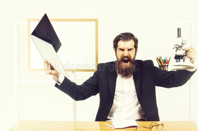 Angry businessman with laptop. Angry man businessman male scientist hipster with laptop and microscope shouts furiously in office with board for copy space on royalty free stock photography