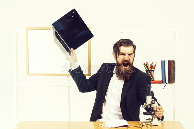 Angry businessman with laptop. Angry man businessman male scientist hipster with laptop and microscope shouts furiously in office with board for copy space on stock photo