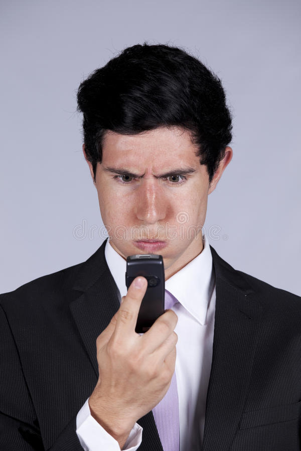 Angry businessman looking to his cellphone stock photos