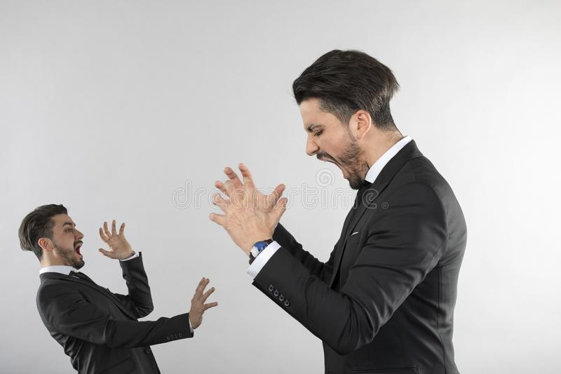 Angry businessman screaming and throwing hands. White background stock photography