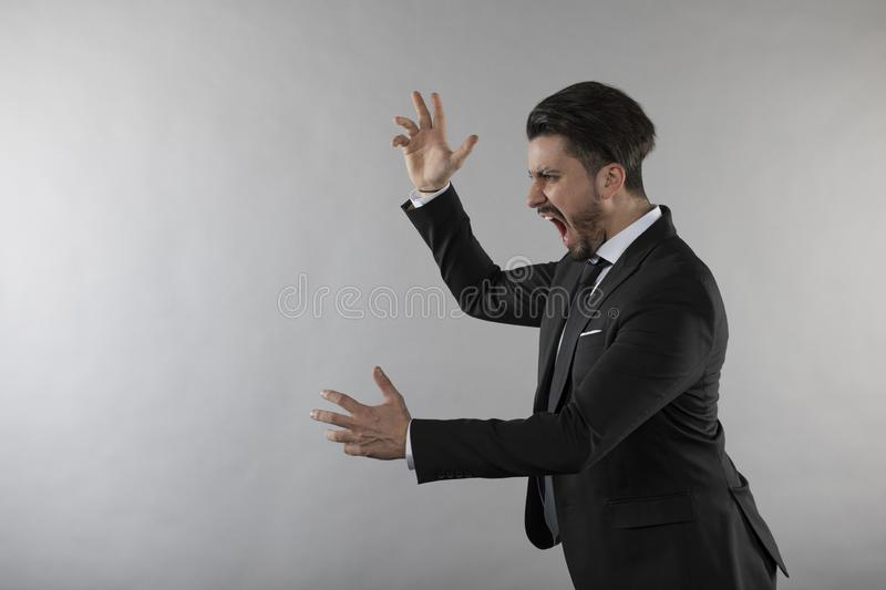 Angry businessman screaming and throwing hands. White background royalty free stock image