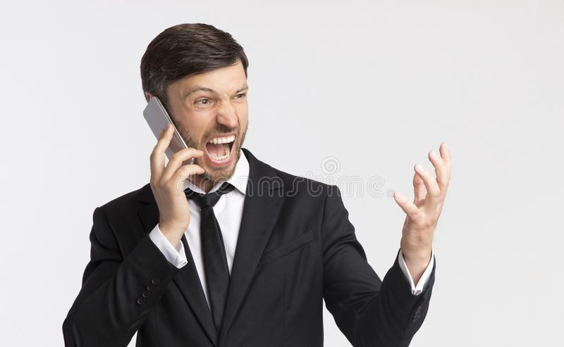 Angry Businessman Shouting Talking On Cellphone Over White Background. Phone Rage. Furious Businessman Shouting Talking On Cellphone Over White Studio Background stock photo
