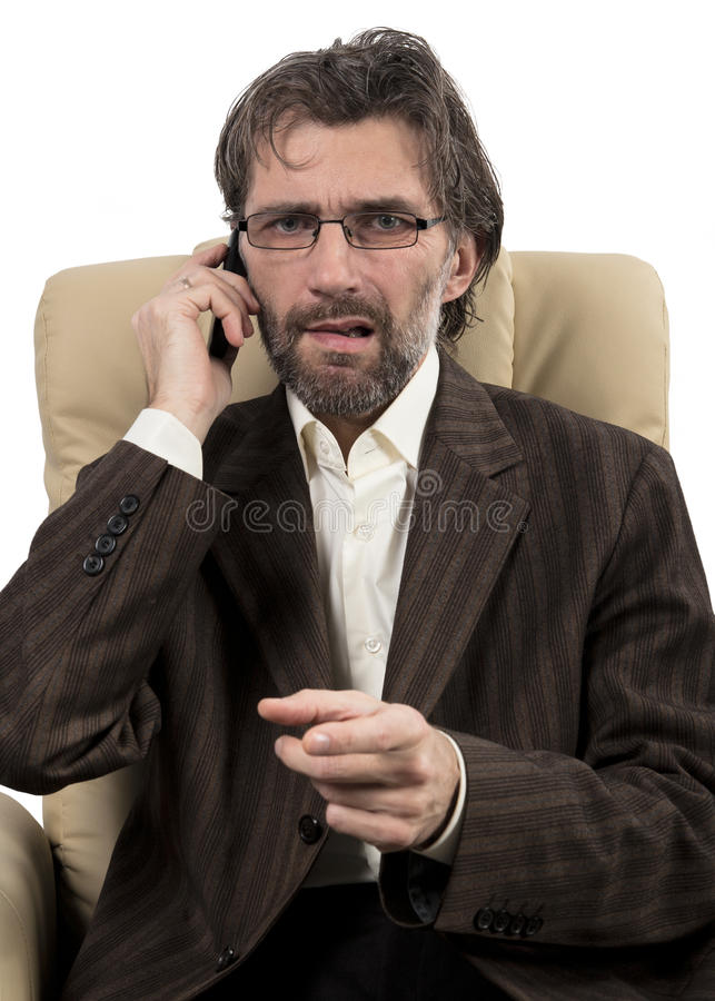 Angry businessman sitting with mobile phone. Angry businessman sitting in chair with mobile phone isolated white stock photo