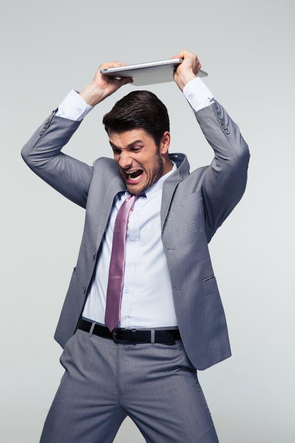 Angry businessman smashing his laptop stock photography