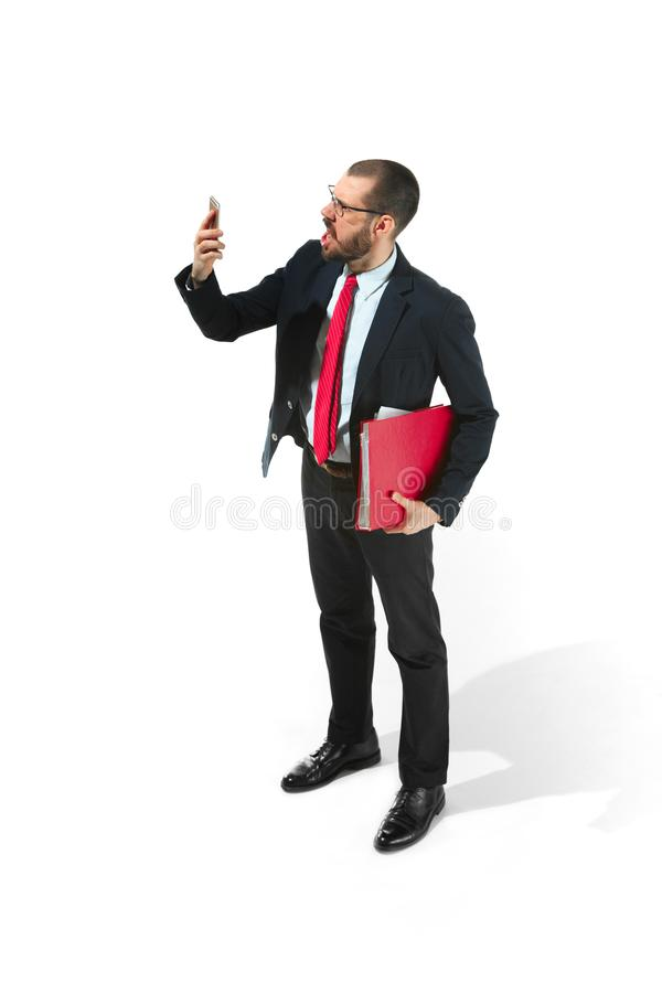 Angry businessman talking on the phone with folder in hand over white background in studio shooting royalty free stock photo