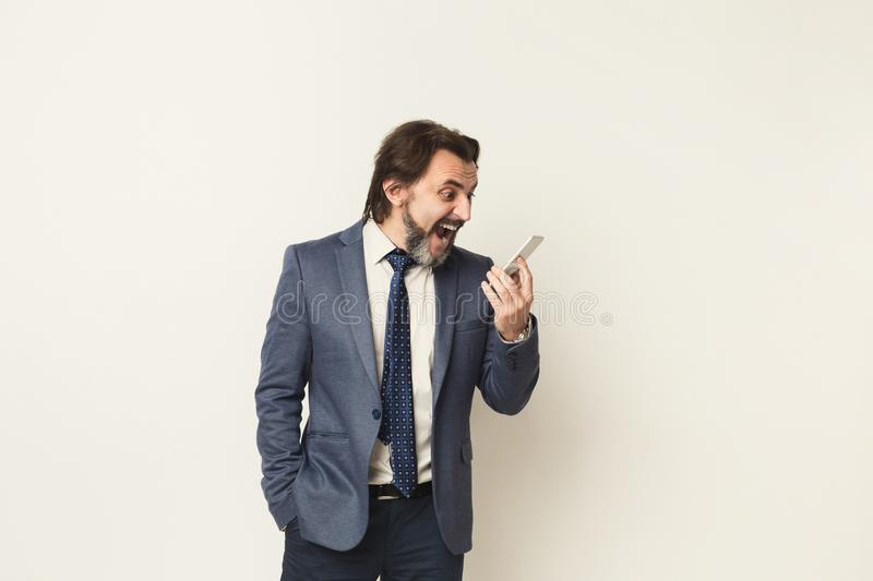 Angry businessman crying on phone at white background royalty free stock image
