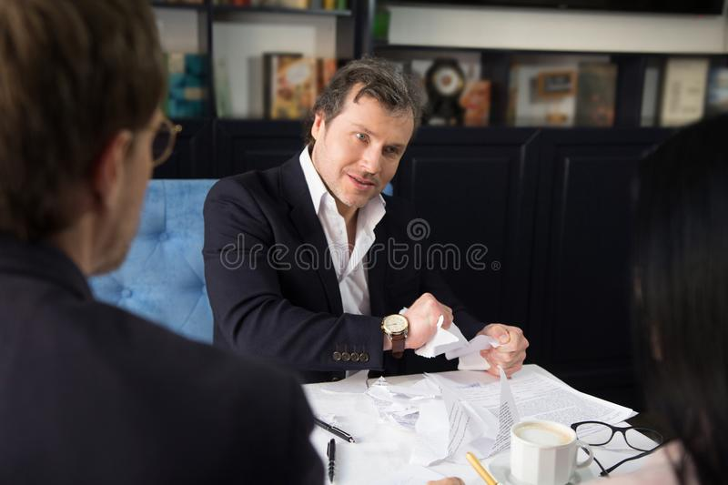 Business people discussing agreement condition. Angry businessman torning agreement. Does not want to sign it royalty free stock photos
