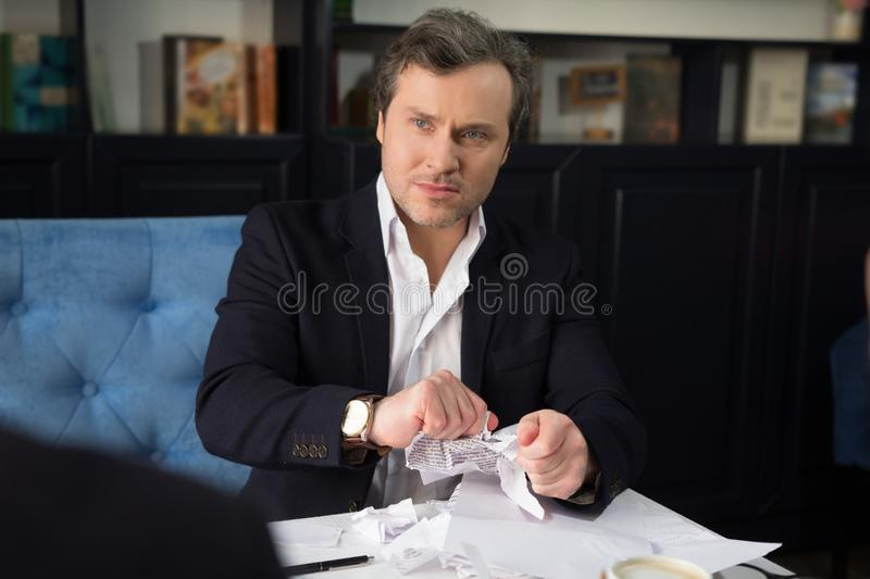 Business people discussing agreement condition. Angry businessman torning agreement before his partners. Business concept stock photos