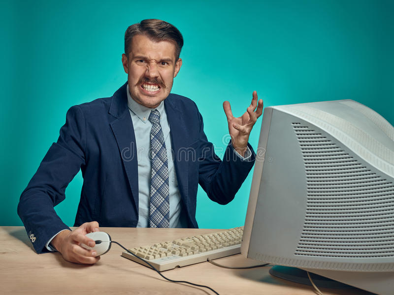 Angry businessman using a monitor against blue background. Angry fury businessman using a monitor against a blue studio background royalty free stock photo
