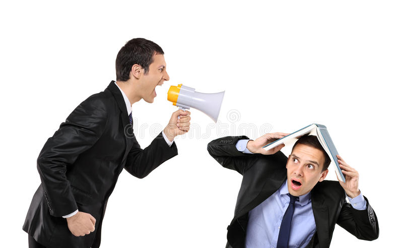 Angry businessman yelling to a man. Angry businessman yelling via megaphone to a man who is covering his head with book stock photo