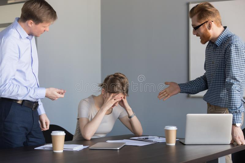 Angry businessmen shouting at female colleague blaming for failu stock photos