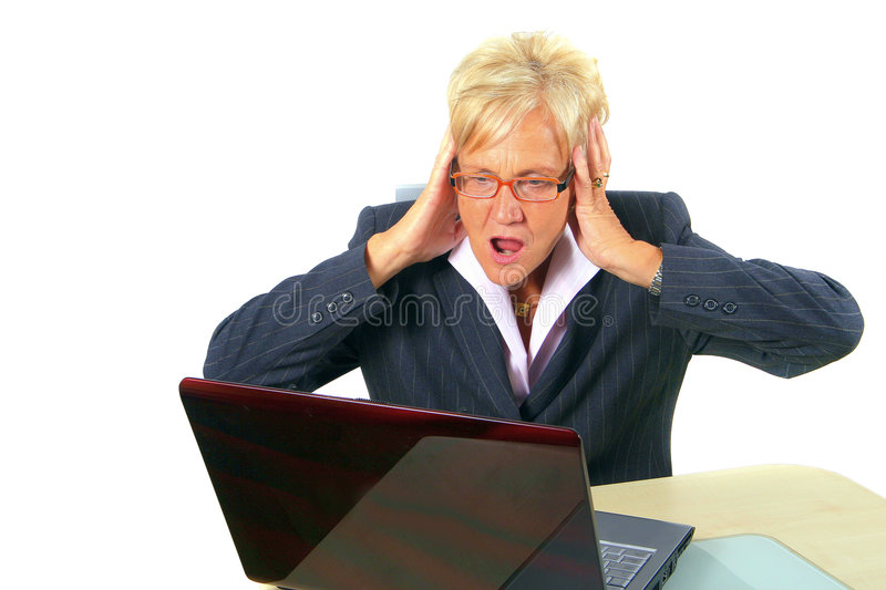 Angry Businesswoman. A businesswoman in her sixties in front of a laptop shocked with her hands on her head. Isolated over white stock photography