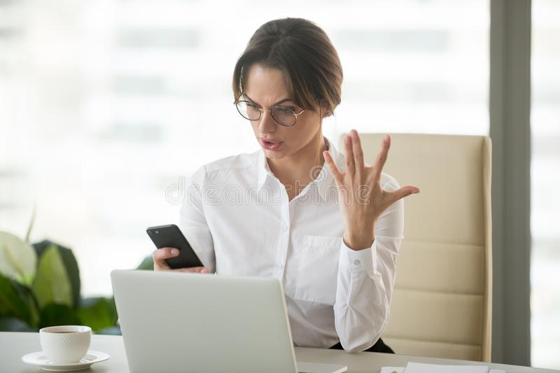 Angry businesswoman annoyed with stuck not working phone in offi. Angry outraged businesswoman annoyed with missed call or no signal on stuck not working mobile royalty free stock image