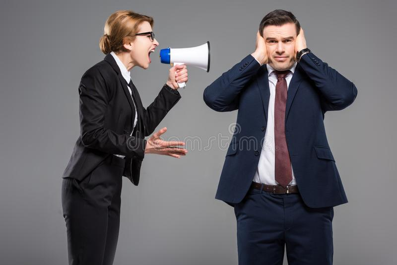 Angry businesswoman with bullhorn screaming at businessman. Isolated on grey feminism concept stock photo