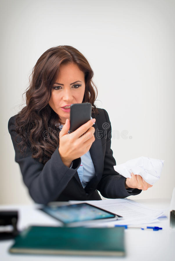 Angry businesswoman. Angry businesswoman with phone in office stock photography