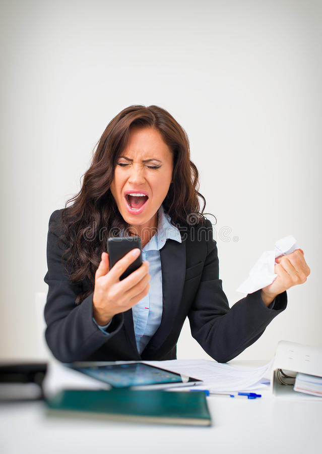 Angry businesswoman. Angry businesswoman with phone in office royalty free stock photography