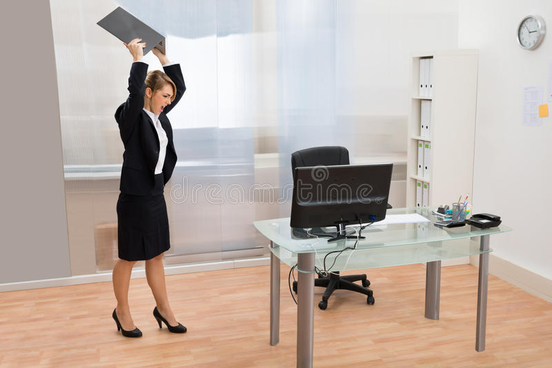Angry Businesswoman Throwing Laptop royalty free stock images