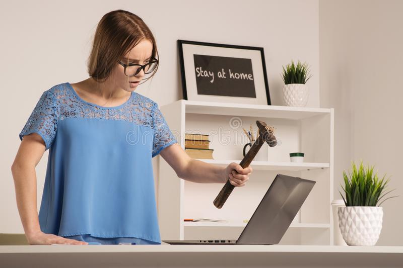 Angry businesswoman went mad with hammer and laptop royalty free stock photography