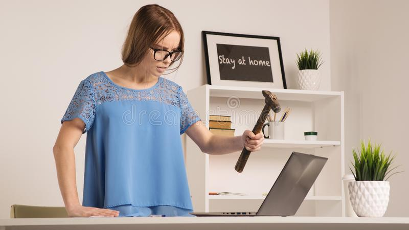 Angry businesswoman went mad with hammer and laptop royalty free stock images