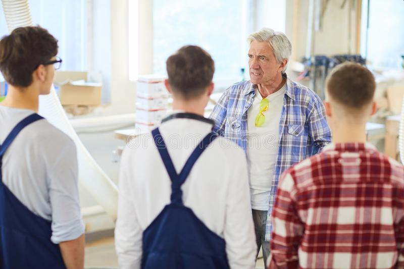 Angry carpenter yelling at young employees stock images