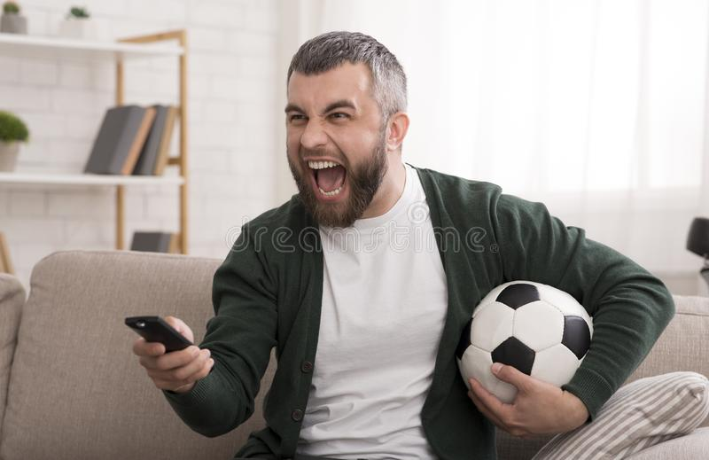 Angry caucasian man watching football game on TV stock photo