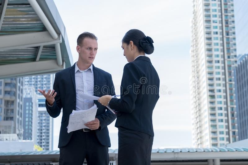 Angry caucasian manager stand and holding document on hand, he blaming employee women for work mistakes. Angry caucasian manager stand and holding document on stock photos