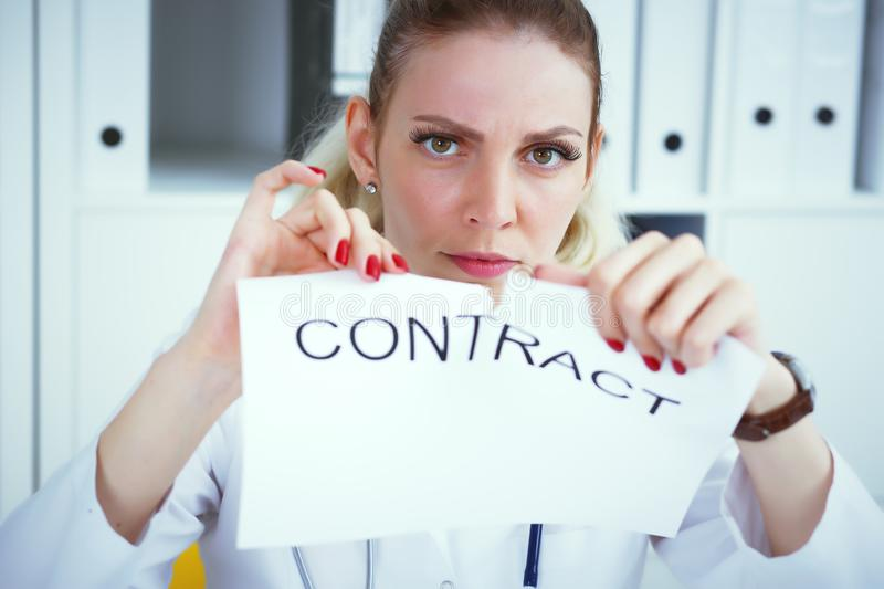 Angry Caucasian woman tears agreement documents in front of camera closeup. Young woman tears agreement documents in front of camera closeup stock photography