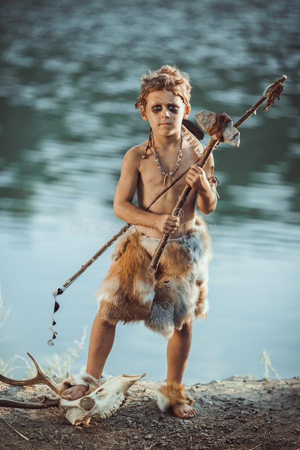 Angry caveman, manly boy with ancient primitive weapon hunting outdoors. Ancient prehistoric warrior. Heroic movie look. Angry caveman, manly boy with stone axe royalty free stock image
