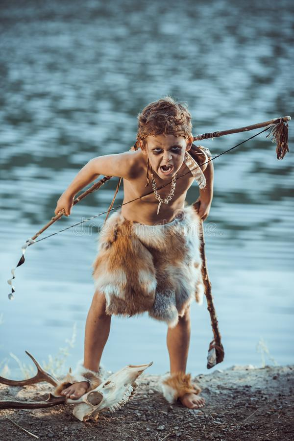Angry caveman, manly boy with primitive weapon hunting outdoors. Ancient prehistoric warrior. Heroic movie look. Angry caveman, manly boy with stone axe and bow royalty free stock image