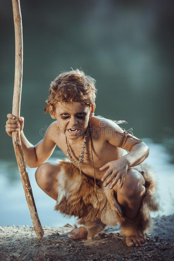 Angry caveman, manly boy with staff hunting outdoors. Ancient warrior. Angry caveman, manly boy with staff hunting. Prehistoric tribal boy outdoors on nature stock photos