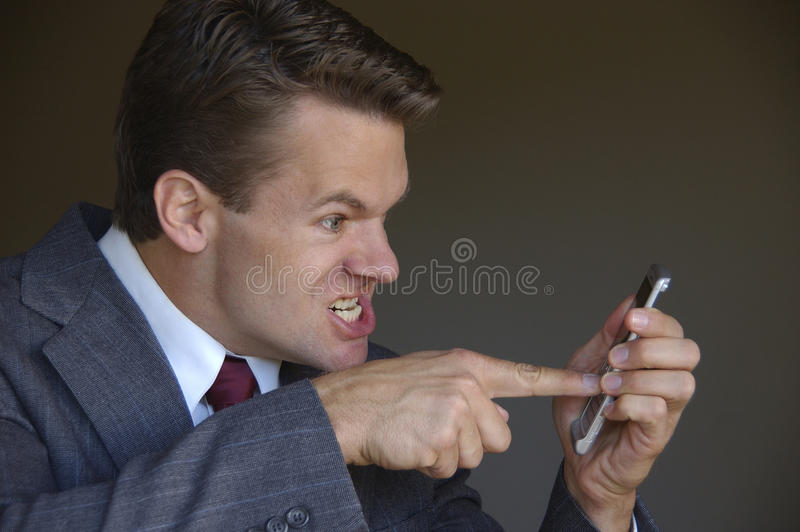 Angry at cell phone. Business man gets angry with cell phone stock images