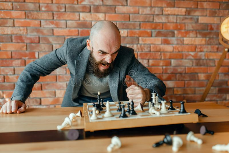 Angry chess player beats his fist on the board. With the pieces. Stressed chessplayer in a fit of anger, intellectual tournament indoors. Chessboard on wooden stock image
