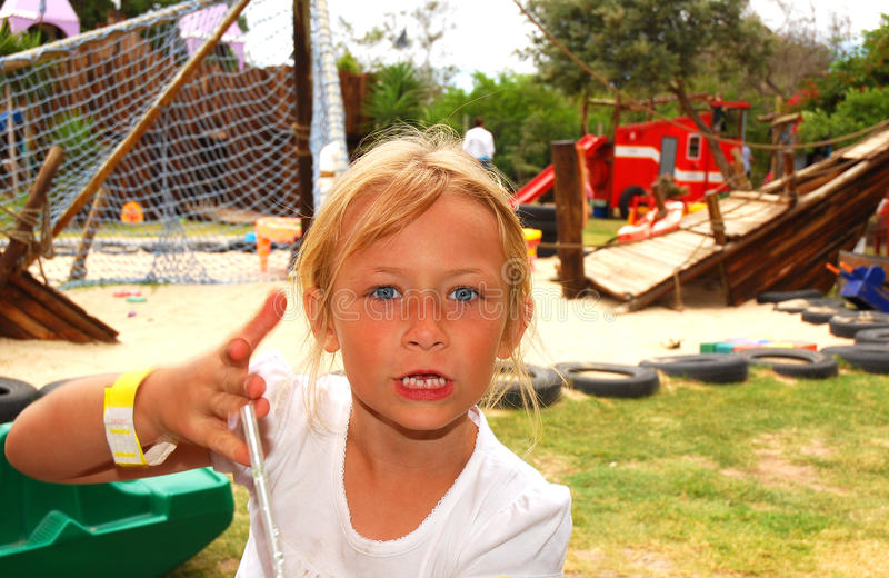 Angry child on playground. Outdoor portrait of a blond cute little Caucasian girl child with angry expression in her beautiful face stock photography