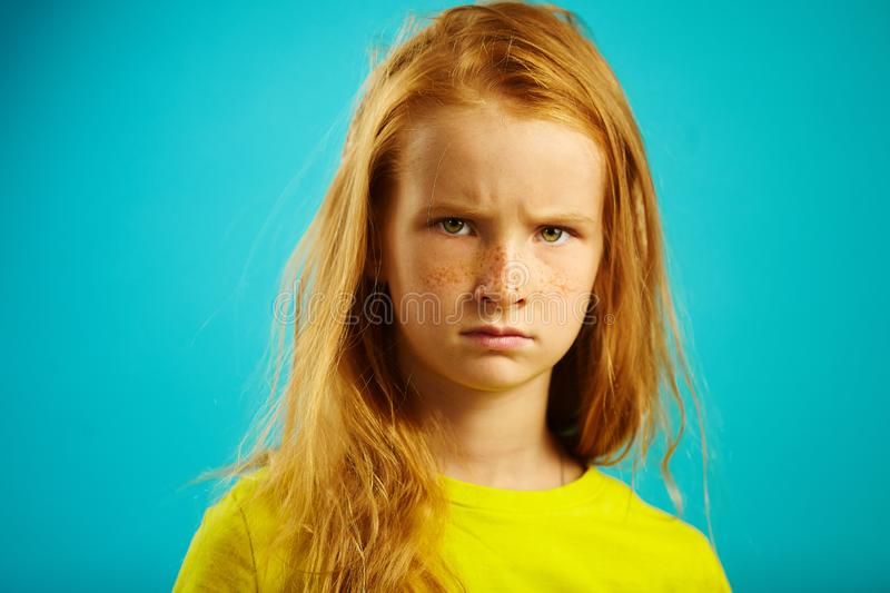 Angry children girl with red hair on blue. Horizontal close-up image of unhappy child stock images