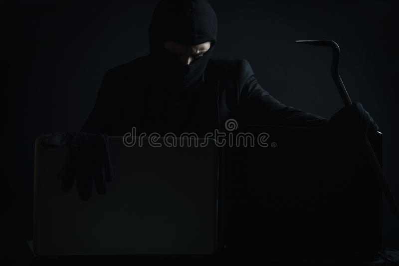 Angry computer hacker in suit stealing data from laptop with cro royalty free stock image