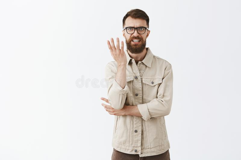 Angry and confused displeased mad european guy with long beard in black glasses clenching teeth frowning shrugging with. Raised palm in clueless gesture arguing royalty free stock images