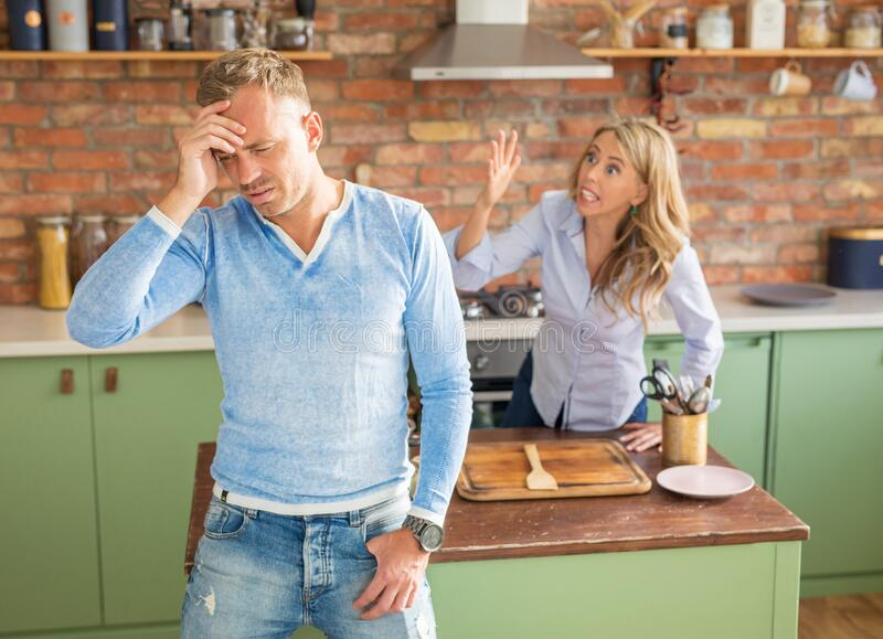 Angry couple arguing in kitchen stock photography